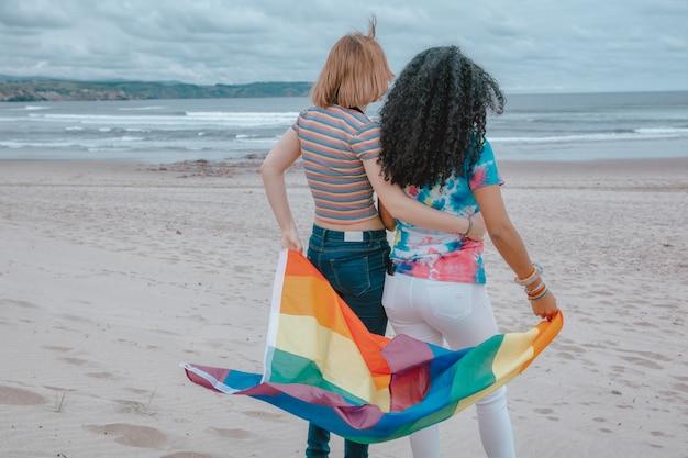 Joven pareja de lesbianas moviendo la bandera del orgullo gay en una playa de arena mientras mira una puesta de sol romántica - imagen