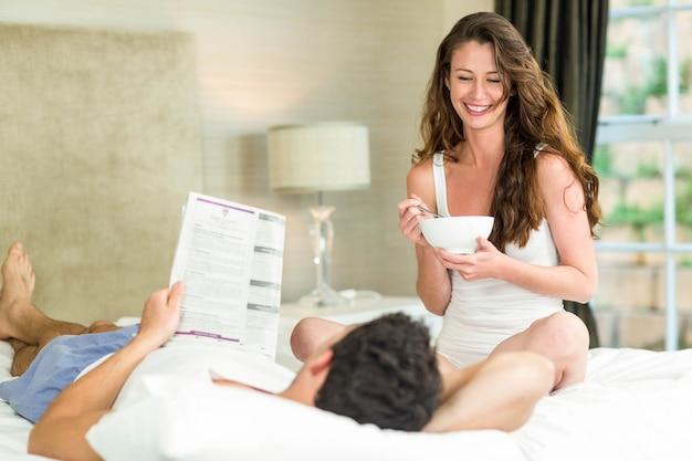 Joven pareja leyendo periódico y desayunando en dormitorio