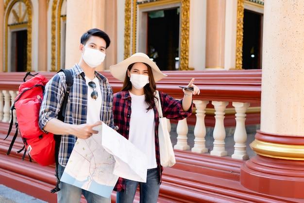 Joven pareja de mochileros asiáticos en un hermoso templo durante las vacaciones en tailandia, una mujer bonita usa un sombrero señalando a donde quieren ir, sostienen un mapa de papel y un teléfono inteligente para verificar la dirección