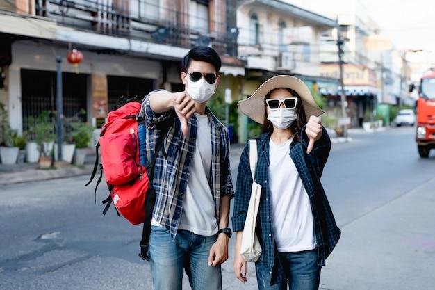 Joven pareja de mochileros en mascarilla y gafas de sol hacen una marca cruzada de prohibición con golpe hacia abajo