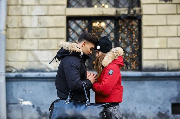 Una joven pareja de moda camina en la ciudad en navidad.