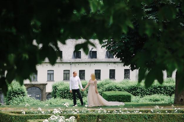 Una joven pareja de moda camina en la ciudad en verano, la joven lleva un vestido de lujo