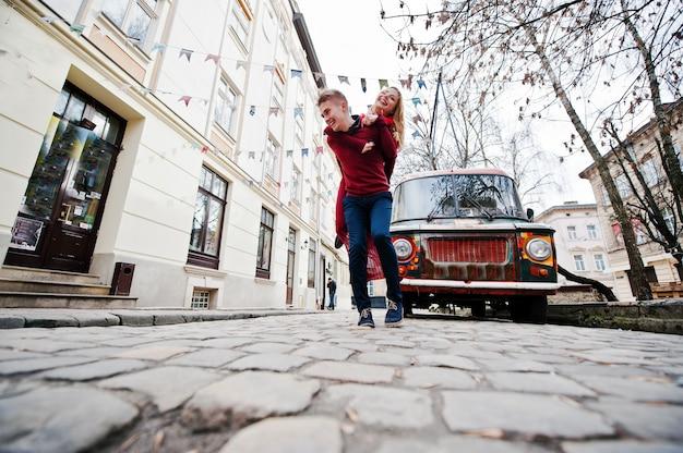 Joven pareja de moda elegante hermosa en un vestido rojo en la historia de amor en la ciudad vieja