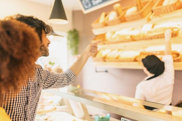 Joven pareja moderna en panadería, elegir una barra de pan.