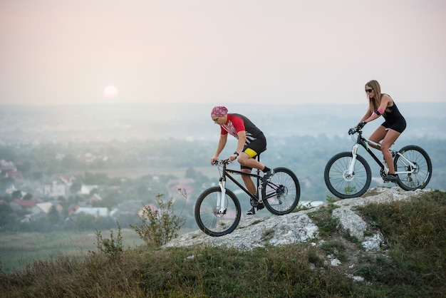 Joven pareja montando en bicicleta de montaña en el fondo de la hermosa puesta de sol