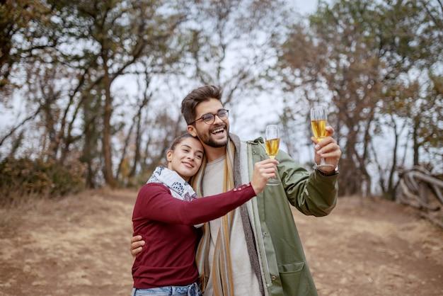 Joven pareja multicultural alegre vestido casual abrazando, de pie en la naturaleza en otoño y brindando por aniversario. otoño.