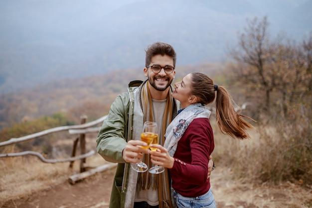 Joven pareja multicultural alegre vestido casual abrazando, de pie en la naturaleza en otoño y brindando por aniversario.