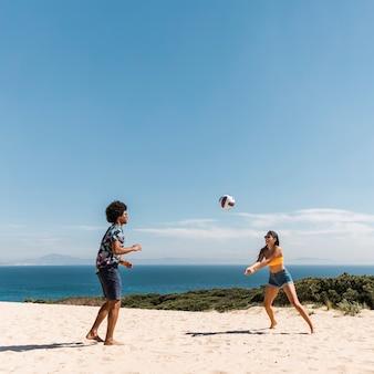 Joven pareja multicultural jugando voleibol en la playa