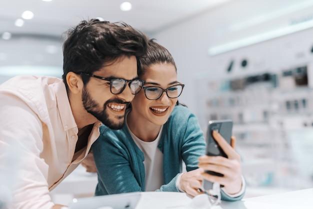 Joven pareja multicultural sonriente con anteojos probando nuevo teléfono inteligente en la tienda de tecnología.