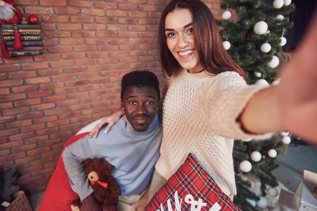 Joven pareja multiétnica reunión navidad abrazando a casa. año nuevo. humor festivo de un hombre y una mujer.