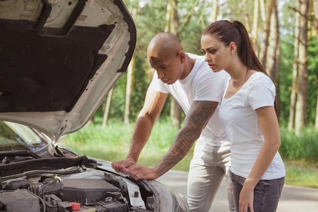 Joven pareja multirracial con un auto roto en medio de la carretera