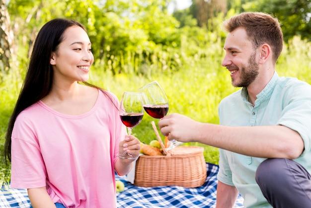 Joven pareja multirracial enamorada haciendo picnic en la naturaleza