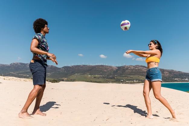 Joven pareja multirracial jugando juego con pelota en la playa