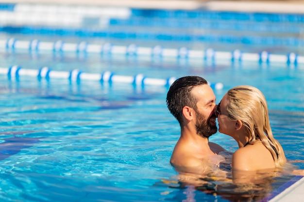 Joven pareja está nadando en la piscina y riendo