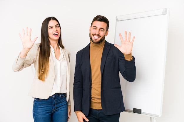 Joven pareja de negocios caucásico aislado mostrando el número diez con las manos.