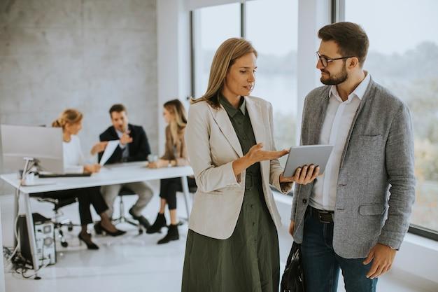 Joven pareja de negocios discutiendo con tableta digital en la oficina con jóvenes trabaja detrás de ellos