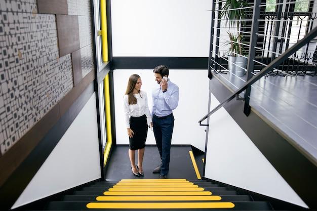 Joven pareja de negocios en las escaleras en la oficina