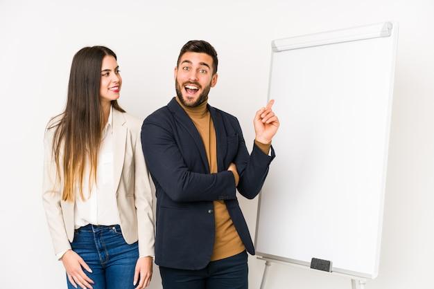 Joven pareja de negocios sonriendo alegremente señalando con el dedo lejos