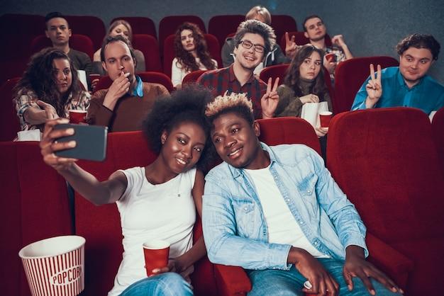 Joven pareja negra toma fotos en el cine.