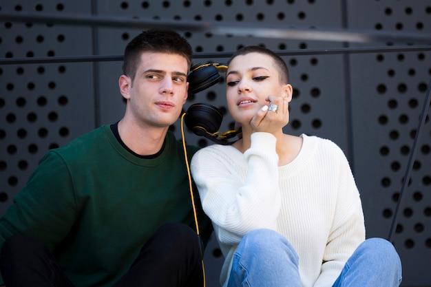 Joven pareja de pelo corto escuchando música con auriculares