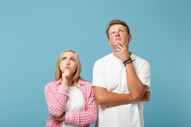Joven pareja pensativa dos amigos hombre y mujer en blanco rosa camisetas vacías en blanco posando