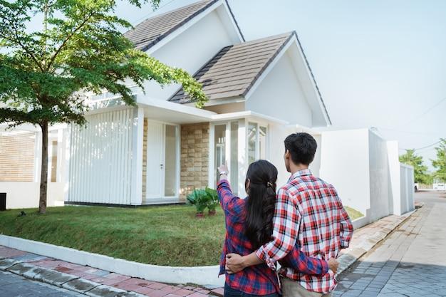 Joven pareja de pie frente a su nueva casa