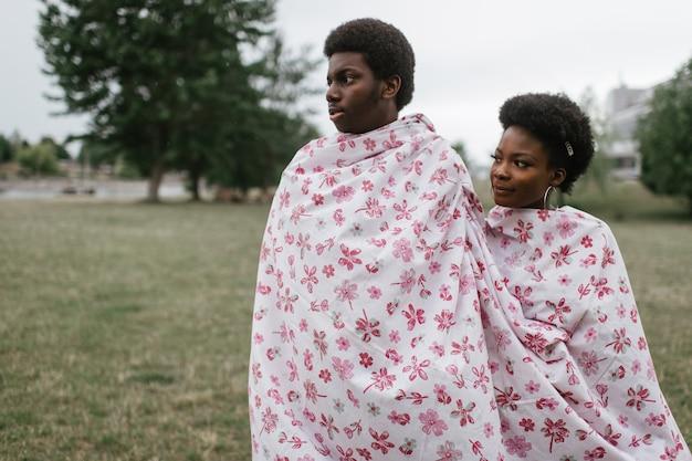 Joven pareja de piel oscura envuelta en la hoja de pie juntos al aire libre.