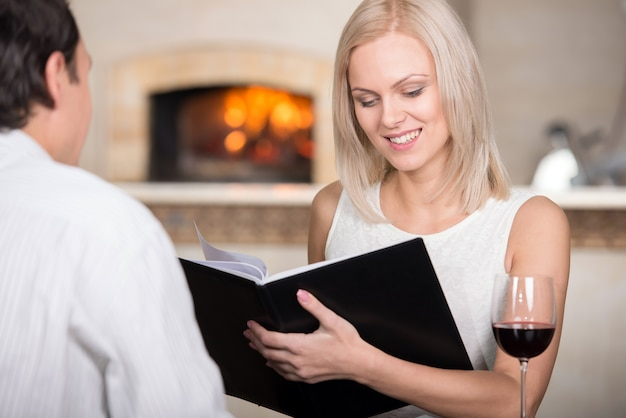 Joven pareja en restaurante animando con vino tinto.