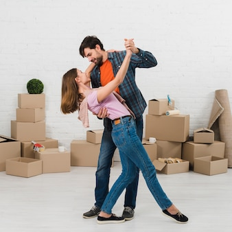 Joven pareja romántica bailando frente a cajas de cartón