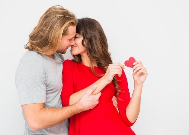 Joven pareja romántica besándose contra el fondo blanco