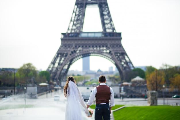 Joven pareja romántica cerca de la torre eiffel en la madrugada en parís, francia