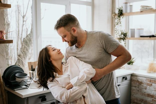 Joven pareja romántica en la cocina. la chica de la camisa blanca.