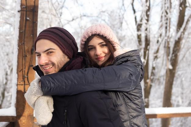 Joven pareja romántica se divierte al aire libre en invierno antes de navidad