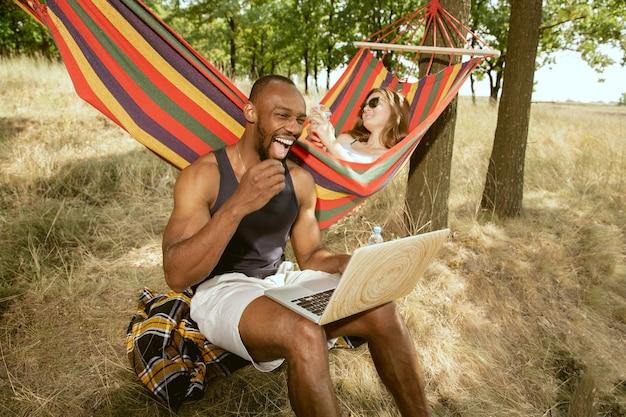 Joven pareja romántica internacional multiétnica al aire libre en la pradera en un día soleado de verano. hombre afroamericano y mujer caucásica haciendo picnic juntos. concepto de relación, verano.
