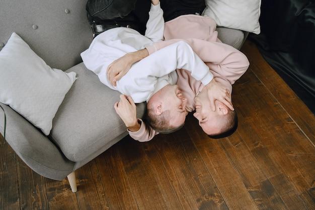 Joven pareja romántica lgbtq pasar el día abrazados y relajándose en el sofá. concepto de estilo de vida familiar diferente.