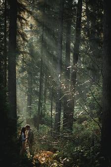 Joven pareja romántica de linda mujer con cabello largo y moreno y barbudo tomados de la mano caminando en el bosque verde y soleado