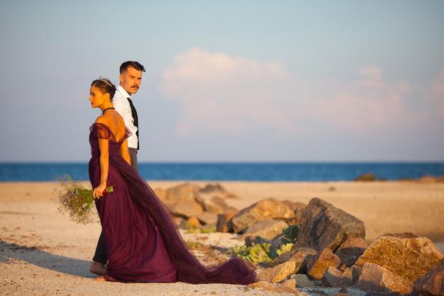 Joven pareja romántica relajante en la playa mirando el atardecer