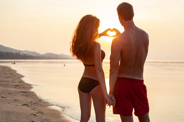 Joven pareja romántica sexy enamorada feliz en la playa de verano juntos divirtiéndose vistiendo trajes de baño mostrando signo de corazón en sundet