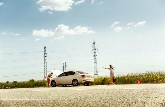 La joven pareja rompió el auto mientras viajaba camino a descansar. están tratando de detener a otros conductores y pedir ayuda o hacer autostop. relación, problemas en la carretera, vacaciones.