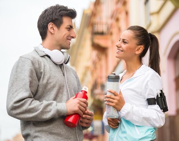 Joven pareja en ropa deportiva con botellas de agua.