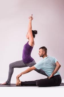 Joven pareja sana hombre y mujer en posición de yoga sobre fondo blanco.