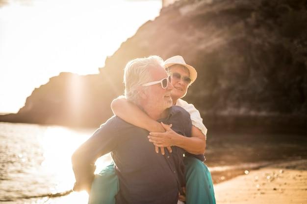 Joven pareja senior enamorada disfruta del horario de verano en la playa