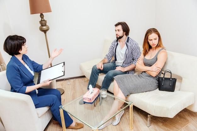 Joven pareja está sentada juntos y mirando a diferentes lados. tienen y argumento. el psicólogo está sentado frente a ellos e intenta ayudarlos. ella les esta hablando a ellos.