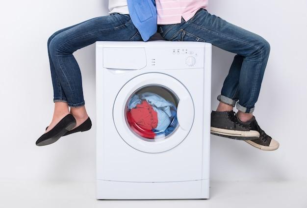 Joven pareja está sentada en la lavadora.