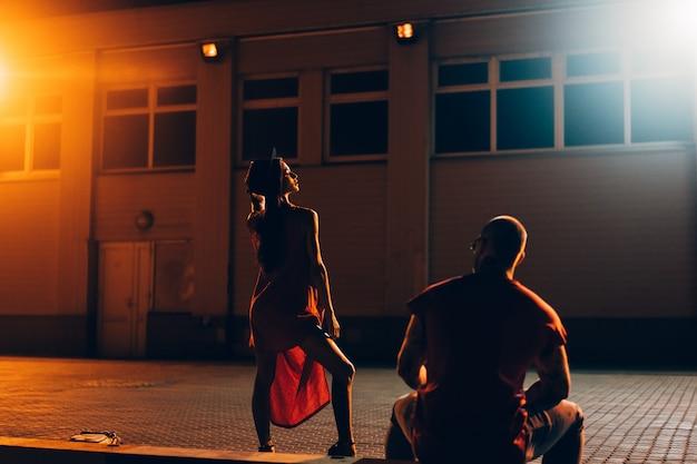 Una joven pareja sexy amantes posan en la calle de la noche de la ciudad.