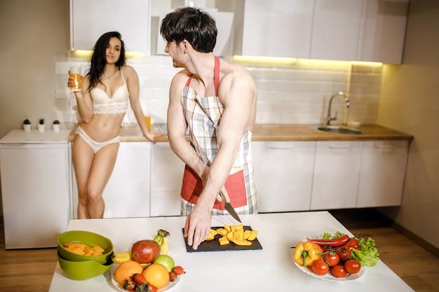 Joven pareja sexy después de la intimidad en la cocina en la noche. el hombre descamisado alegre en delantal corta la fruta y mira a la mujer. ella usa lencería blanca y sostiene un vaso de jugo en la mano.