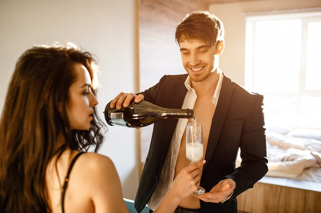 Joven pareja sexy en la sala de estar. alegre buen empresario en traje vertiendo vino espumoso en vaso de mujer. juntos en la sala. sexy souple después de la intimidad.