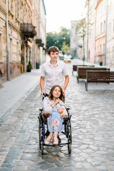 Joven pareja en silla de ruedas paseando en la ciudad. mujer joven en silla de ruedas y su novio en el centro de la ciudad vieja