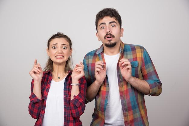 Una joven pareja sobre fondo gris con los dedos cruzados y deseando lo mejor.