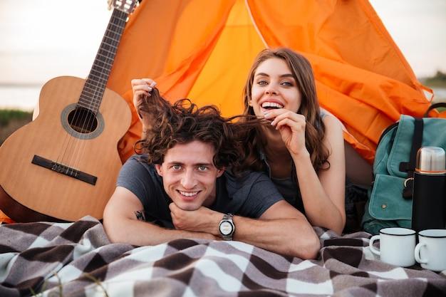 Joven pareja sonriente feliz en el amor divirtiéndose mientras acampa en la playa